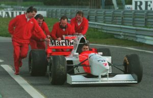 Nigel Mansell being pushed back to the pits by his Mclaren mechanics in the MP4/10, 1995